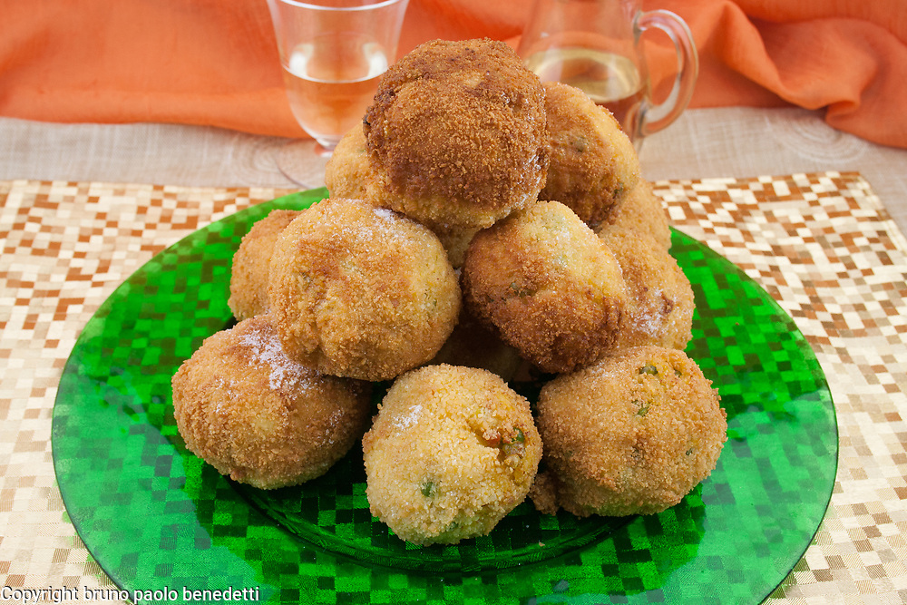 Sicilian aracini, fried rice balls pyramid on green glass dish side view from above with red wine and orange veil on background, italian traditional food