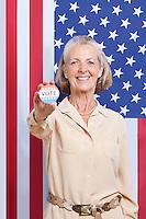 Portrait of senior woman holding election badge against American flag