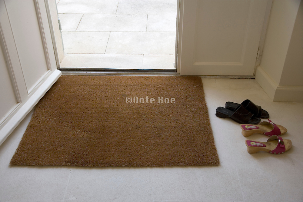 entrance to a domestic house with womam's slippers at the door mat