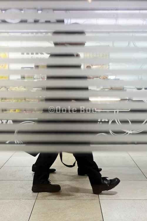 business people walking with blocked view from frosted lines on window Japan