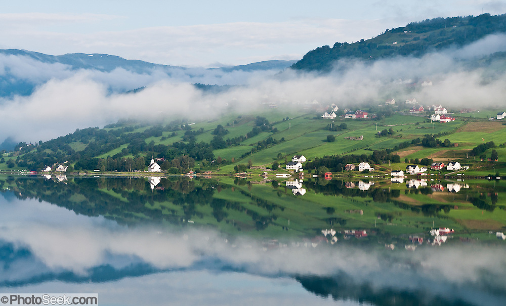 The lake of Hafslovatnet reflects fog, farm buildings and fields in Luster municipality, Sogn og Fjordane county, Norway