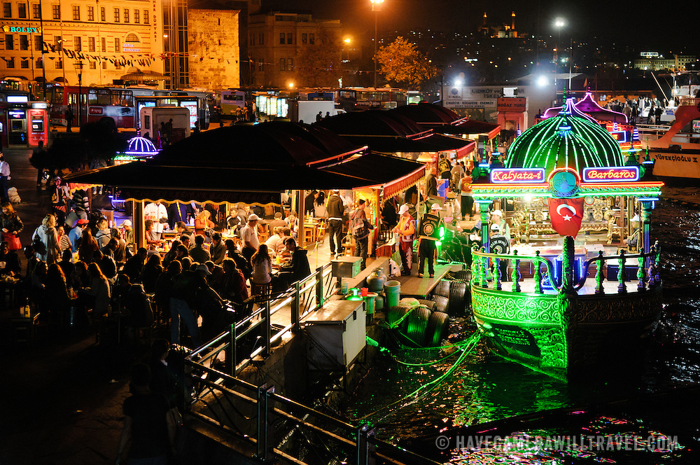 The waterfront district of Eminonu at night, with the grilled fish boats moored to the docks and diners seated to their left.