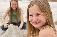 Two girls (10-12) playing in sand on beach  focus on girl on foreground