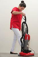 Full length of female housekeeper using vacuum cleaner