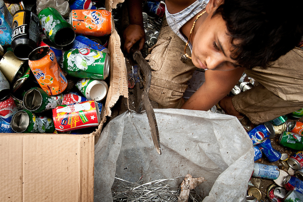 A young boy cuts the tops off of aluminum cans before they can be sent to the smelter.