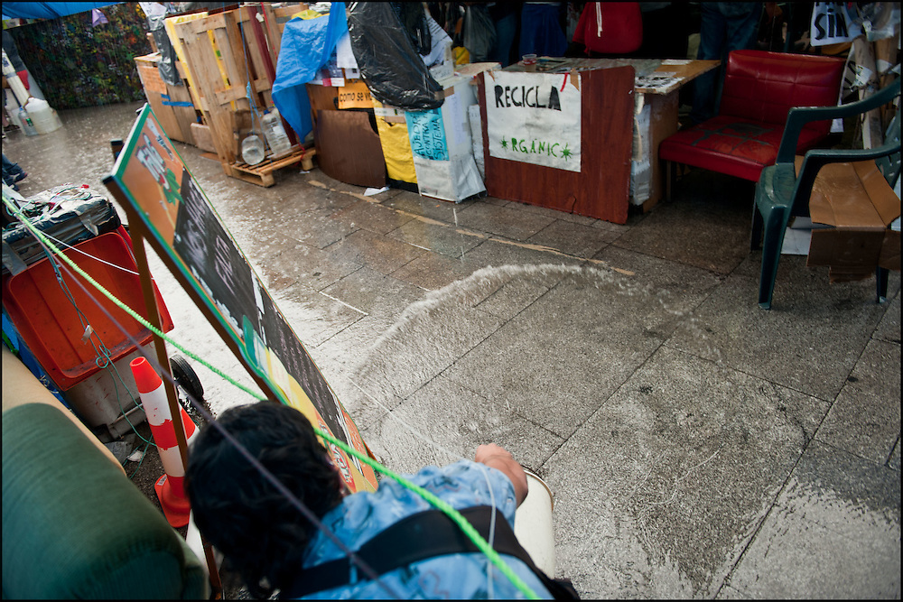 """Des manifestants tentent de se proteger de la pluie et de sauvegarder leur abri de fortune. // Le mouvement spontane du """"15 M"""" (15 mai) compose de citoyens espagnols campe depuis 2 semaines sur la place Puerta Del Sol avec pour revendication la construction d'une democratie nouvelle. Organise en commission les citoyens prennent la parole lors d'assemblee ouverte a tous - Place Puerta Del Sol à Madrid le Juin 2011. ©Benjamin Girette/IP3Press"""
