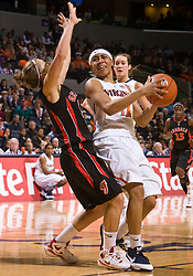 Virginia guard Britnee Millner (12) is fouled on her way to the basket in action against Georgia.  The #15 ranked Virginia Cavaliers defeated the Georgia Lady Bulldogs 62-60 in NCAA Women's Basketball at the John Paul Jones Arena on the Grounds of the University of Virginia in Charlottesville, VA on January 2, 2009.