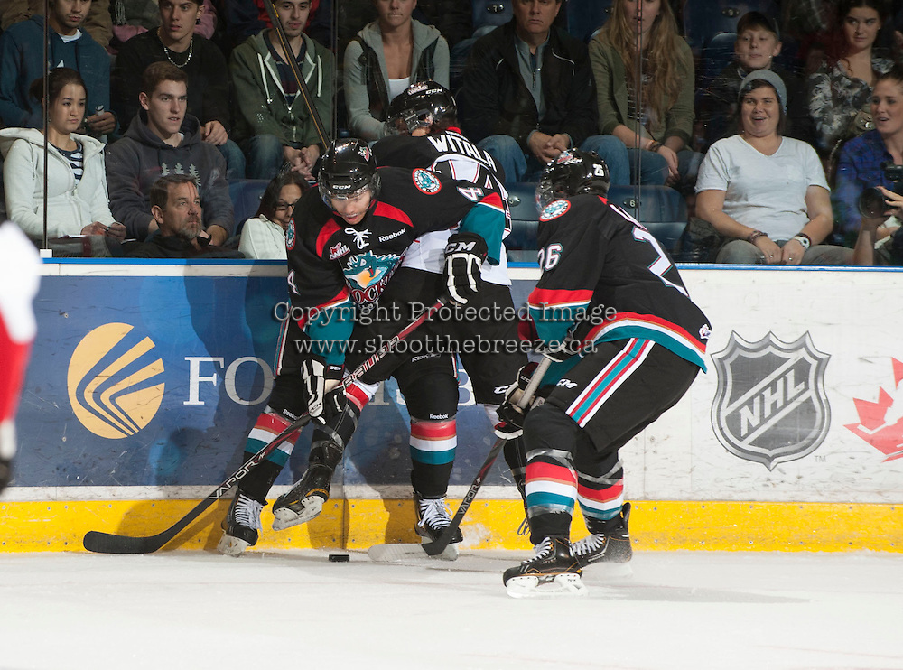 KELOWNA, CANADA - OCTOBER 18:  Madison Bowey #4 and Cole Linaker #26 of the Kelowna Rockets check Chase Witala #14 of the Prince George Cougars into the boards as the Prince George Cougars visit the Kelowna Rockets on October 18, 2012 at Prospera Place in Kelowna, British Columbia, Canada (Photo by Marissa Baecker/Shoot the Breeze) *** Local Caption ***