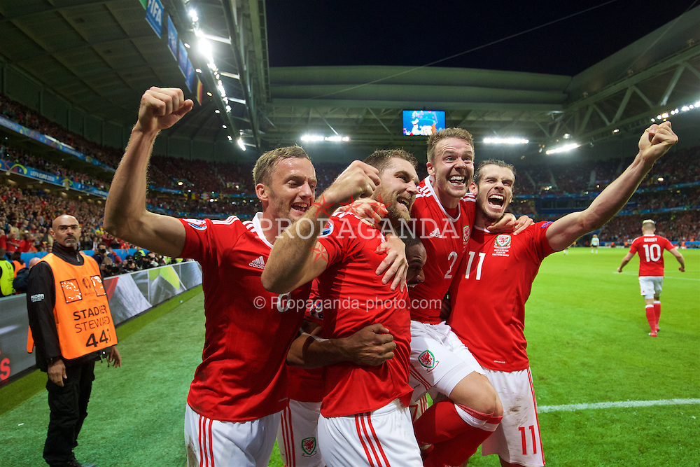 LILLE, FRANCE - Friday, July 1, 2016: Wales' Sam Vokes [18] celebrates scoring the third goal against Belgium to seal a 3-1 victory, with team-mates Andy King, captain Ashley Williams, Chris Gunter and Gareth Bale during the UEFA Euro 2016 Championship Quarter-Final match at the Stade Pierre Mauroy. (Pic by David Rawcliffe/Propaganda)