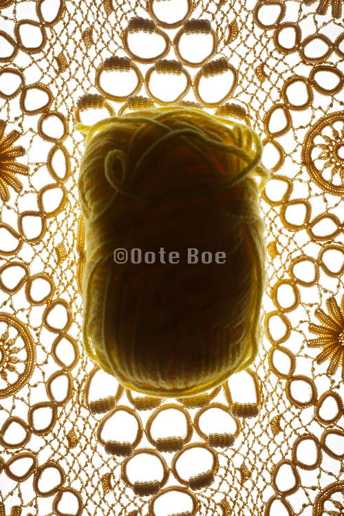 lace fabric with ball of yellow wool knitting yarn