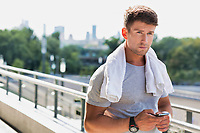 Portrait of young attractive man standing with towel on his shoulders while using smartphone