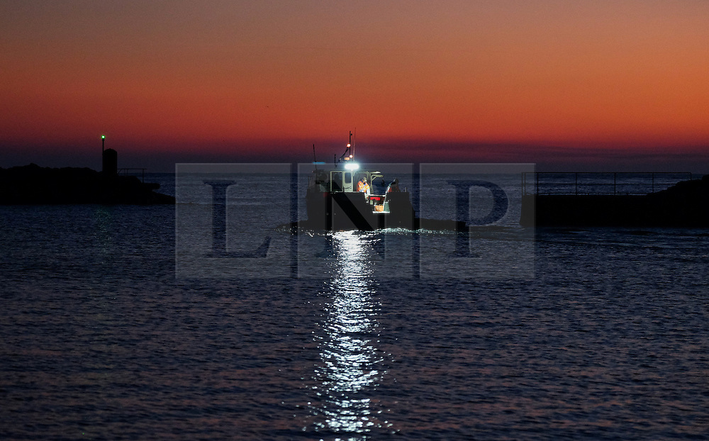 © Licensed to London News Pictures.02/10/15<br /> Staithes, UK. <br /> <br /> A fishing boat heads out of the harbour as dawn breaks in the North Yorkshire village of Staithes on the east coast as the warm autumn weather continues.<br /> <br /> Photo credit : Ian Forsyth/LNP