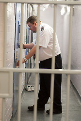 Holding cell in the detention suite of a police station with Group 4 staff, UK