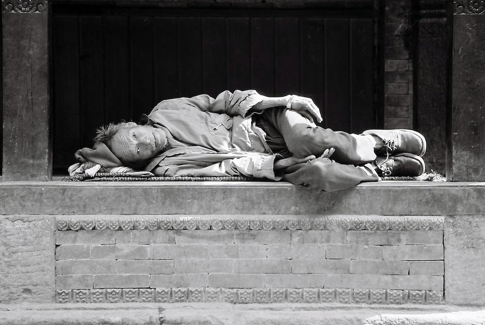 """En fin d'après-midi, dans une ruelle de Bakthapur, un vieil homme se repose sous un """"abris à pèlerins"""". Bhaktapur, Népal. 2008"""