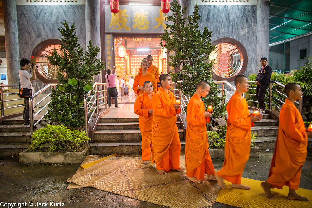 23 OCTOBER 2012 - HAT YAI, SONGKHLA, THAILAND: Buddhist monks lead a procession through the temple on the last day of the Vegetarian Festival at Wat Ta Won Vararum, a Chinese Buddhist temple in Hat Yai. The Vegetarian Festival is celebrated in Thai-Chinese communities throughout Thailand. It is the Thai Buddhist version of the The Nine Emperor Gods Festival, a nine-day Taoist celebration celebrated in the 9th lunar month of the Chinese calendar. For nine days, those who are participating in the festival dress all in white and abstain from eating meat, poultry, seafood, and dairy products. Vendors and proprietors of restaurants indicate that vegetarian food is for sale at their establishments by putting a yellow flag out with Thai characters for meatless written on it in red. PHOTO BY JACK KURTZ
