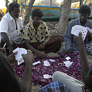 Unemployed fishermen gamble among the wrecked boats and homes of Perumalpettai, a fishing village in Tamil Nadu, India on January 15, 2005, after the area was struck by the Indian Ocean Tsunami on December 26, 2004, killing 37 of the villagers and destroying nearly all of their fishing boats. Generated by an earthquake on the ocean floor, the tsunami devastated the fishing industry along the southeastern coast of India.