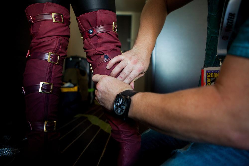 Cosplayer Yaya Han's fiancé Brian Boling helps her put on her boots in preparation for portraying Phoenix from Marvel Avengers Alliance.
