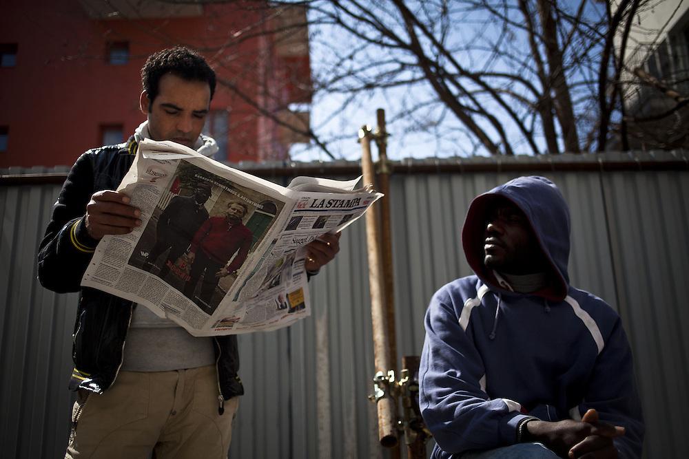 Un ragazzo legge La Stampa. Esterno cortile ex palazzine olimpiche.