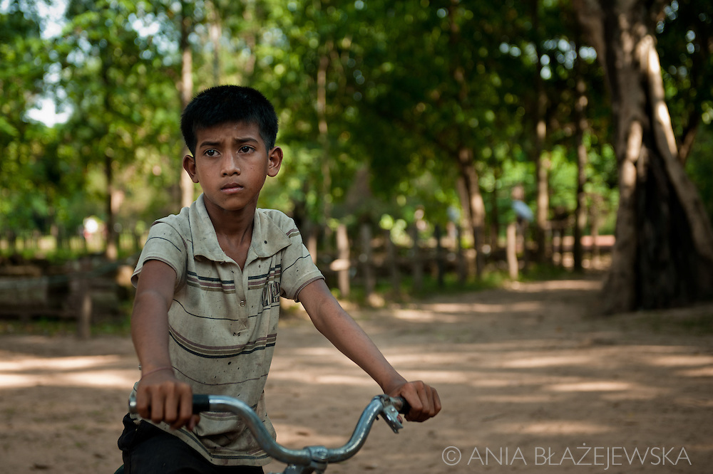 Cambodia. Young sad Khmer boy and his bicycle in ruins of Angkor.