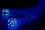 A pair of glowing dice with motion blur against a dark background.