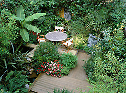 General view from above showing strong design. Statues, decking, architectural plants, seating area & water feature