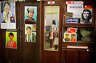 A cabinet inside the NLD headquarter in Yangoon. The mirror reflects a supporter checking a dashboard full of greetings. Myanmar, 2012