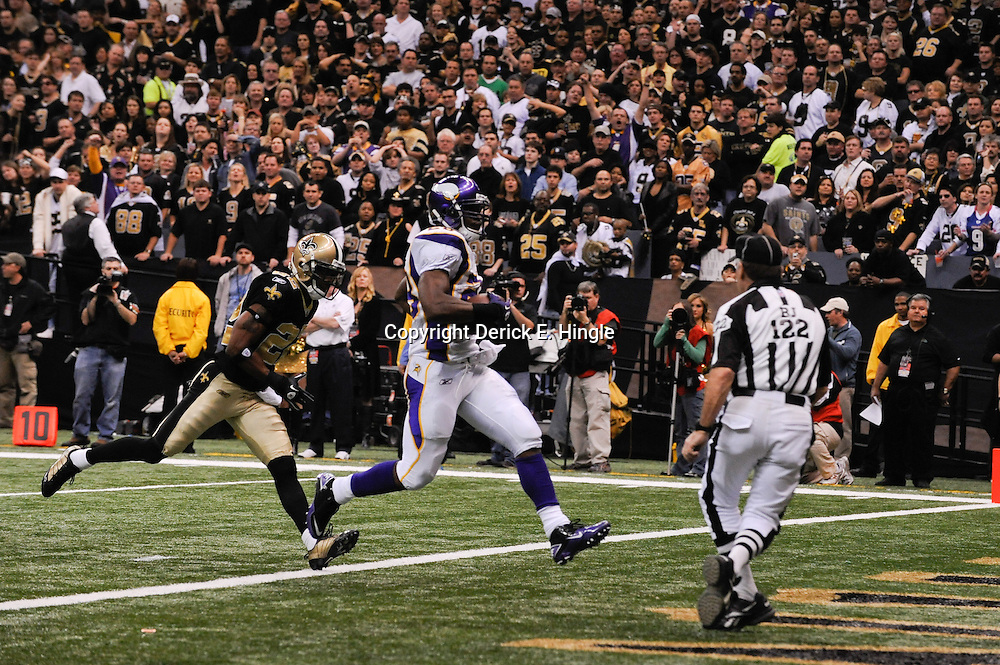 Jan 24, 2010; New Orleans, LA, USA; Minnesota Vikings running back Adrian Peterson (28) runs past New Orleans Saints cornerback Tracy Porter (22) for a touchdown during a 31-28 overtime victory by the New Orleans Saints over the Minnesota Vikings in the 2010 NFC Championship game at the Louisiana Superdome. Mandatory Credit: Derick E. Hingle-US PRESSWIRE