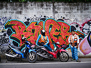 19 SEPTEMBER 2018 - BANGKOK, THAILAND: Motorcycle taxis in front of a wall of graffiti at the Queen Sirikit MRT (subway) stop.      PHOTO BY JACK KURTZ