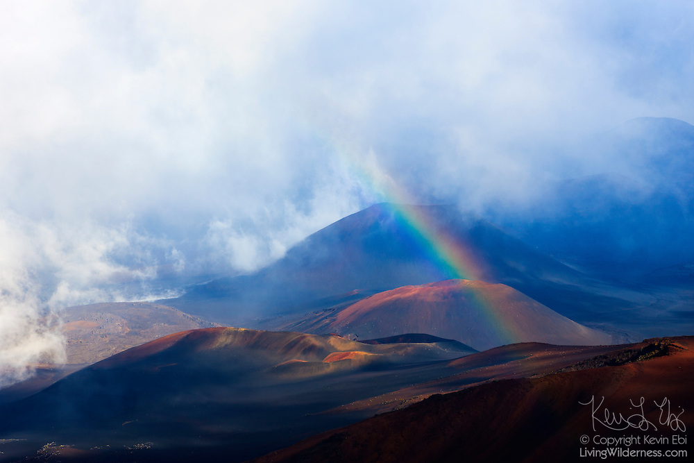 The late afternoon sun shines into a heavy rain storm, forming rainbows over the crater at Haleakala National Park, Maui, Hawaii.