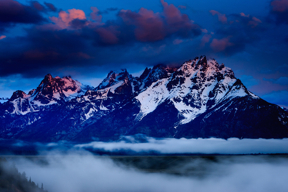 The sun rises through a morning break in the clouds over the Teton Range in Grand Teton National Park.