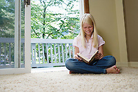 Girl (7-9) sitting cross-legged reading book smiling