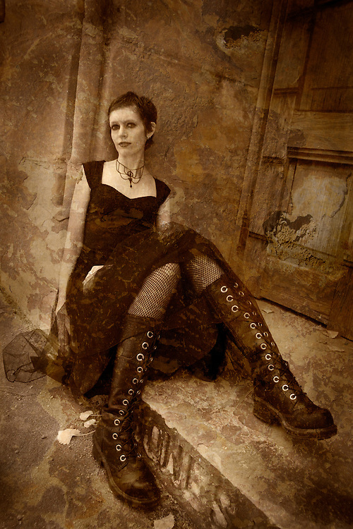 A young woman wearing a black dress and long lace up boots sitting on a step near to a door