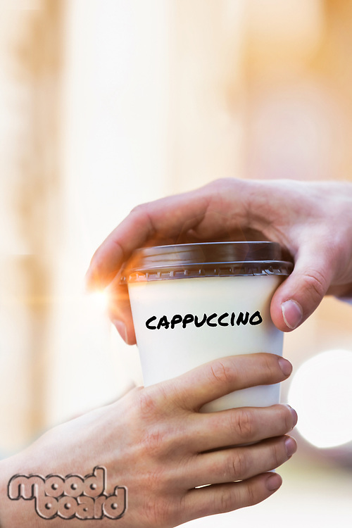 Close up photo of businesswoman giving businessman a cup of cappuccino