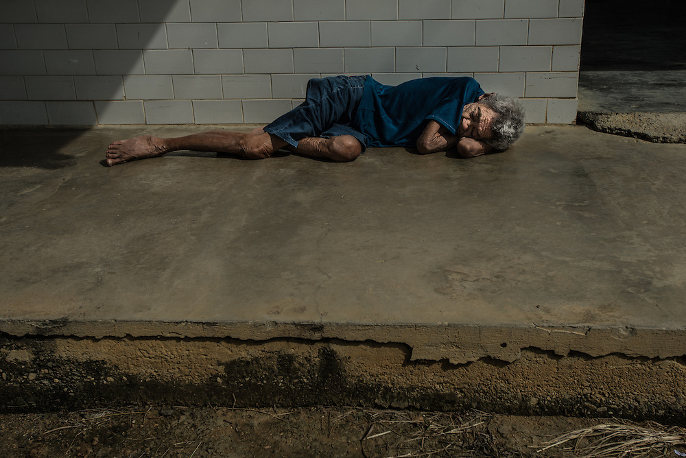 BARQUISIMETO, VENEZUELA - JULY 28, 2016: Schizophrenic patient, <br /> Maria Guzman sleeps on the ground in the women&rsquo;s ward patio area. Her age is unknown, but staff estimate she is between 70 and 80 years old.  The economic crisis that has left Venezuela with little hard currency has also severely affected its public health system, crippling hospitals like El Pampero Psychiatric Hospital by leaving it without the resources it needs to take care of patients living there, the majority of whom have been abandoned by their families and rely completely on the state to meet their basic needs, and who could live much more fulfilling lives if they had the medicines that they need. The hospital does not even have basic hygiene or cleaning supplies.  There is no soap, no shampoo, no tooth paste, no toilet paper.  Patients relieve themselves in the common areas and patio area, and clean themselves only with water. Nearly every patient is infected with scabies because they do not have the resources to bathe properly or to have their threadbare, misfitted clothes washed as often as needed. To make matters worse, the hospital only has running water a few hours a day.  PHOTO: Meridith Kohut