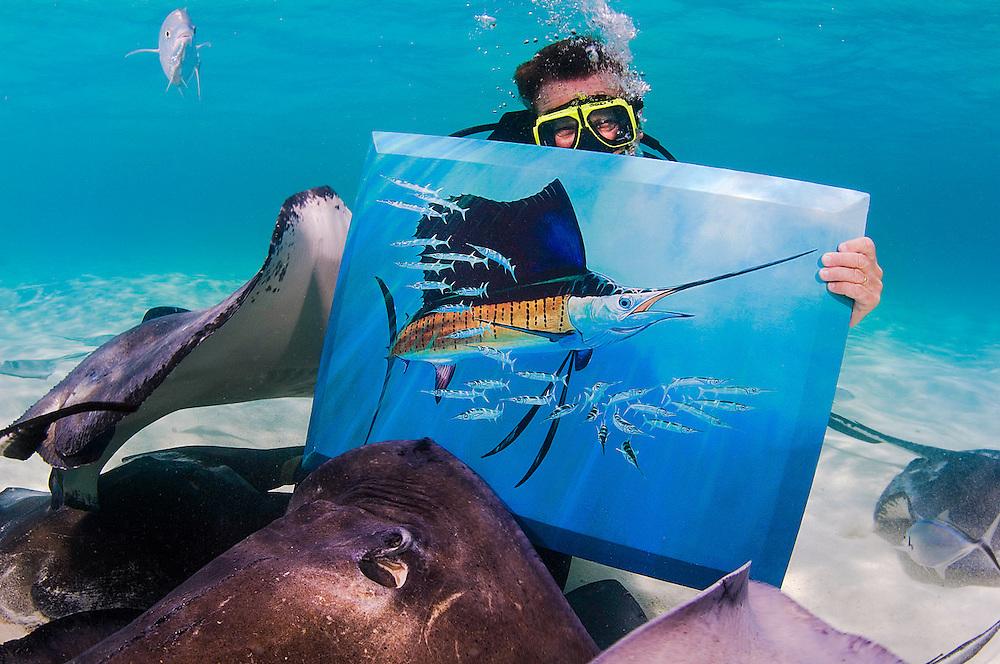 Guy Harvey with a waterproof painting at Stingray Sandbar, Grand Cayman.