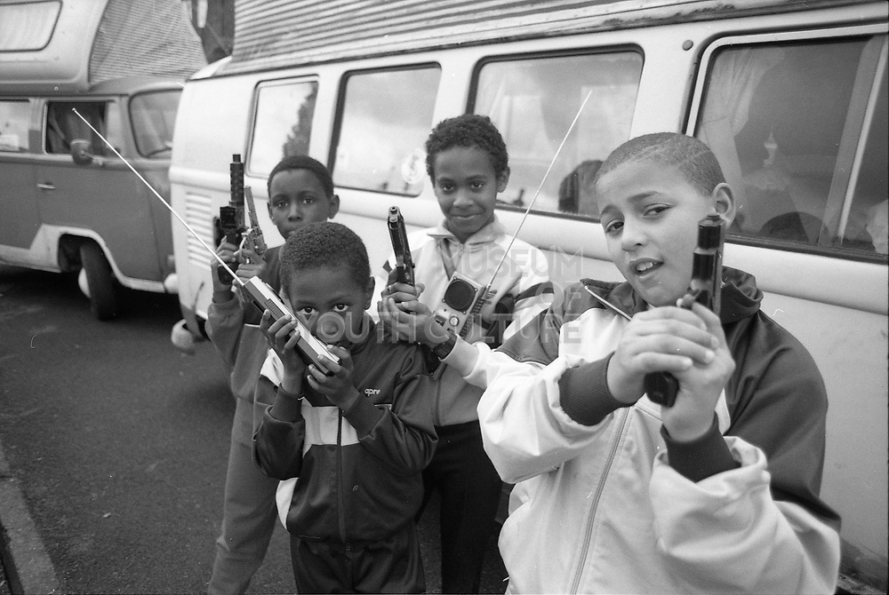 Kids outside campervan with toy guns and walkie-talkies, 1990s, UK.