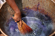 A young girl mixing purple dye with a whisk in a metal bucket to dye material that she sells in a local market, Bamako, Mali.