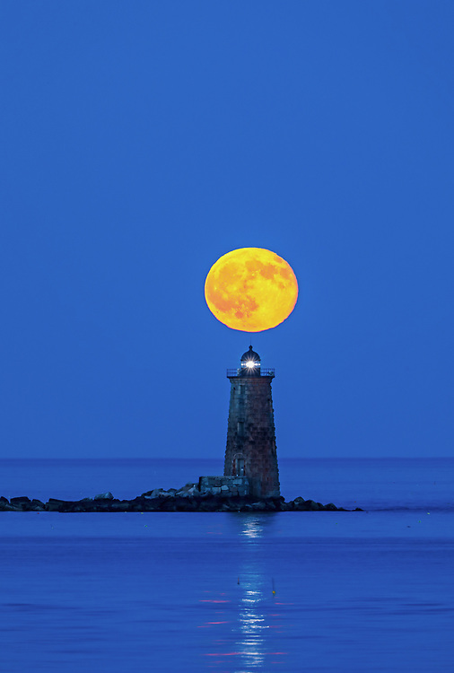 New England lighthouse photography featuring the Whaleback Light with buck full moon in southern Maine near the New Hampshire border. This historic New England lighthouse is located near Portsmouth, NH and is also known as Whaleback Light or Whaleback Ledge Lighthouse. A rising full moon always attracts a lot of nature lovers and photographers alike and there was no difference last night. Originally, I was inspired by the tall and old lighthouse structure out in the ocean that tells the story of bracing Mother Nature for a century and more. After setting up tripod and camera I patiently waited for the moonrise and when it finally arrived I photographed away to ensure I captured my vision of this unforgettable natural phenomenal.   <br />