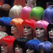 Women's mannequin heads with colored hair fashion wigs at street vendors sidewalk stall on Prince Street in the SOHO district of lower Manhattan, New York, NY USA