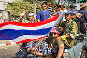 "01 FEBRUARY 2014 - BANGKOK, THAILAND: Thai anti-government protestors get into their pickup trucks after closing the polling place in the Din Daeng section of Bangkok. Thais went to the polls in a ""snap election"" Sunday called in December after Prime Minister Yingluck Shinawatra dissolved the parliament in the face of large anti-government protests in Bangkok. The anti-government opposition, led by the People's Democratic Reform Committee (PDRC), called for a boycott of the election and threatened to disrupt voting. Many polling places in Bangkok were closed by protestors who blocked access to the polls or distribution of ballots. The result of the election are likely to be contested in the Thai Constitutional Court and may be invalidated because there won't be quorum in the Thai parliament.    PHOTO BY JACK KURTZ"