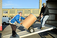 Two men haul a drum container up a ramp and into a truck at Worth a Second Look, a second hand store in Kitchener, Ontario, Canada. The two men are taking part in Job Cafe, a program of The Working Centre and the owner of Worth a Second Look.