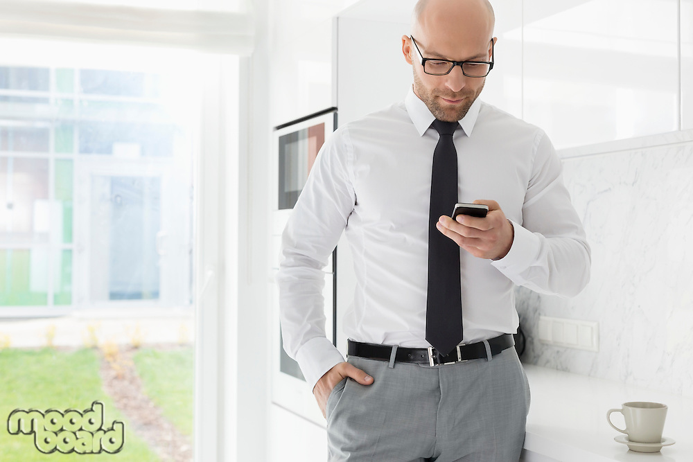 Mid adult businessman text messaging through smart phone at home