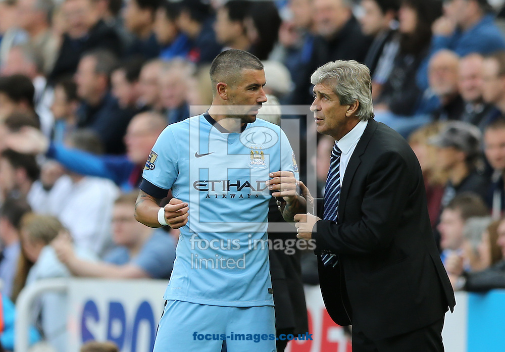 Manchester City manager Manuel Pellegrini (right) gives instructions to Aleksandar Kolarov during the Barclays Premier League match at St. James's Park, Newcastle<br /> Picture by Simon Moore/Focus Images Ltd 07807 671782<br /> 17/08/2014