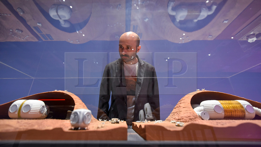 """© Licensed to London News Pictures. 17/10/2019. LONDON, UK. A staff member views """"Mars Habitat series showing the construction sequence"""", 2018, by Foster+Partners. Preview of """"Moving to Mars"""" at the Design Museum. The exhibition explores how sending humans to Mars is a frontier for science as well as design and features over 200 exhibits from NASA, the European Space Agency together with new commissions.  The show is open 18 October to 23 February 2020.  Photo credit: Stephen Chung/LNP"""