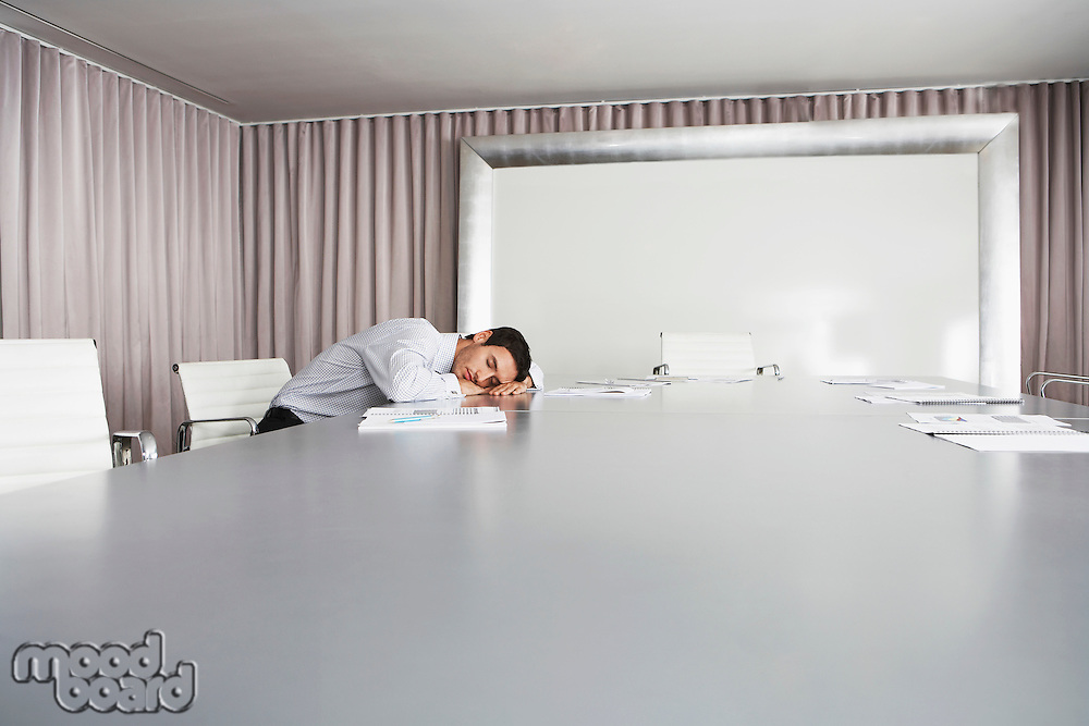 Businessman Sleeping in Conference Room