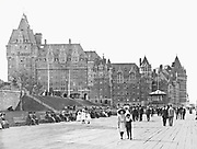 The Mont-Carmel wing of the Chateau Frontenac and the Dufferin Terrace, photograph, 1910, from the Archives of the Chateau Frontenac, Quebec City, Quebec, Canada. The Chateau Frontenac opened in 1893 and was designed by Bruce Price as a chateau style hotel for the Canadian Pacific Railway company or CPR. This photograph was taken before it was extended in 1924 by William Sutherland Maxwell. The building is now a hotel, the Fairmont Le Chateau Frontenac, and is listed as a National Historic Site of Canada. The Historic District of Old Quebec is listed as a UNESCO World Heritage Site. Copyright Archives Chateau Frontenac / Manuel Cohen