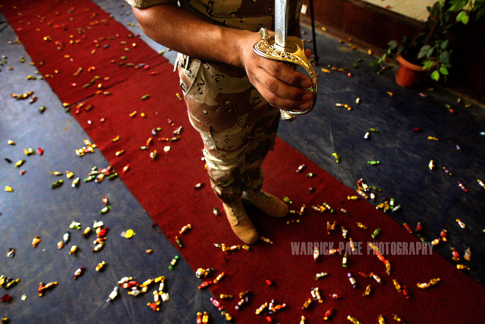 IRAQ, BAGHDAD - JULY 14: An Iraqi Armed Forces soldiers stand at attention amidst a candy-covered floor during their graduation ceremony from officer training at the Rustamiyah Military Academy, July 14, 2008 on the outskirts of Baghdad, Iraq. Mothers of the graduating soldiers threw handfuls of candy over the soldiers during the ceremonies. Having joined in the midst of Iraq's civil war last year, 232 new army and air force lieutenants graduated from the military academy. The academy, founded by the British in 1924, was destroyed and looted after the fall of Baghdad before being reopened by the US-led coalition in 2005. Rebuilding the Iraqi army has been a major challenge for coalition forces since the Coalition Provisional Authority and Bush Administration disbanded it in 2003. The total number of Iraqi Security Forces (ISF), which includes military and police, numbers almost 600,000 personnel and is expected to take control of primary combat responsibilities by mid-2009. Since early 2008, Iraq's security situation has improved with oil production increasing, record government surplus and easing sectarian tensions. (Photo by Warrick Page)