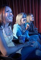 Smiling Young women sitting Watching Movie in theatre