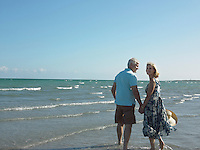 Senior couple walking on tropical beach back view