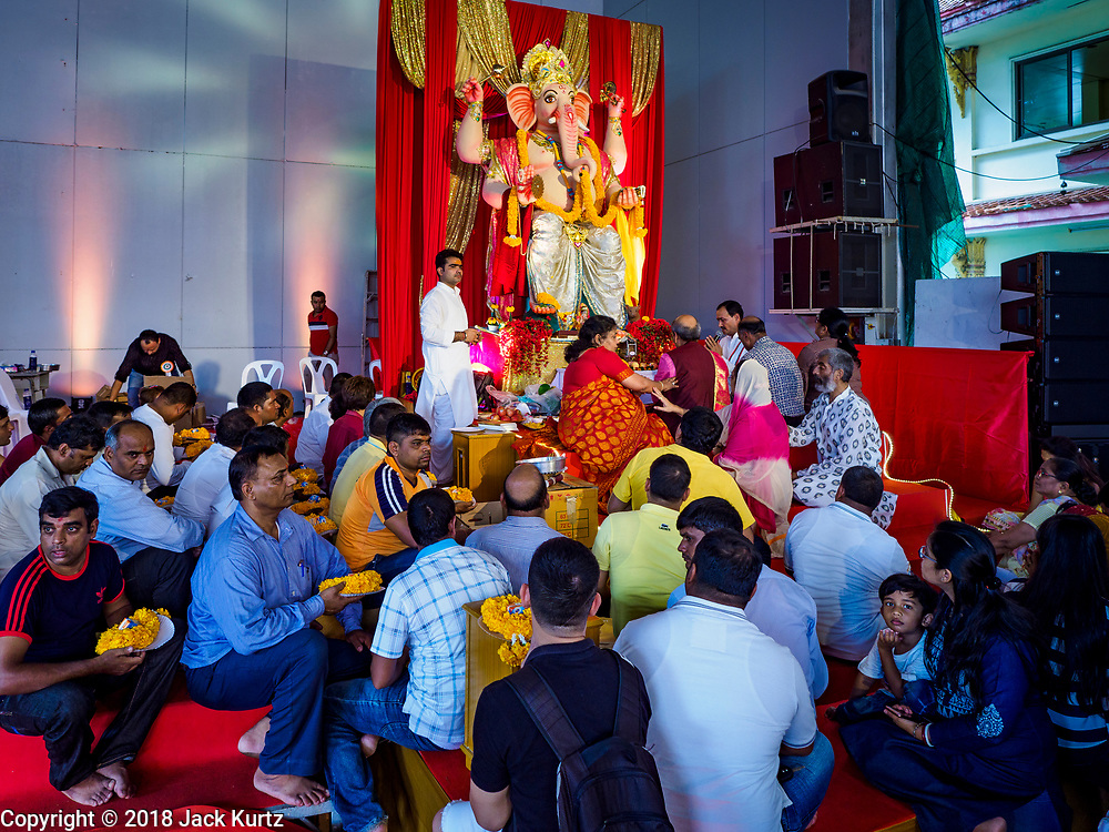 """23 SEPTEMBER 2018 - BANGKOK, THAILAND:  People pray during the Ganesha Festival at Wat Dan in Bangkok. Ganesha Chaturthi also known as Vinayaka Chaturthi, is the Hindu festival celebrated on the day of the re-birth of Lord Ganesha, the son of Shiva and Parvati. The festival, also known as Ganeshotsav (""""festival of Ganesha"""") is observed in the Hindu calendar month of Bhaadrapada, starting on the the fourth day of the waxing moon. The festival lasts for 10 days, ending on the fourteenth day of the waxing moon. Outside India, it is celebrated widely in Nepal and by Hindus in the United States, Canada, Mauritius, Singapore, Thailand, Cambodia, and Burma.    PHOTO BY JACK KURTZ"""